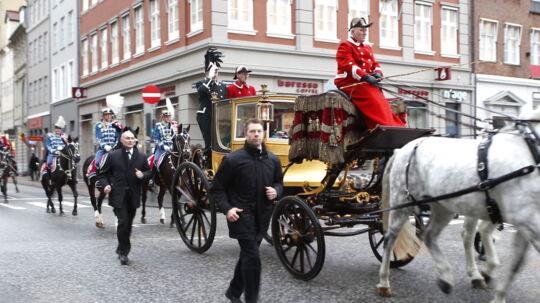 Dronning Margrethe og prins Henrik på vej til nytårskur på Amalienborg i regn og blæst.
