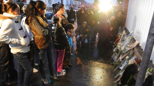 Børn og voksne lægger blomster foran skolen hvor fire personer blev myrdet.
