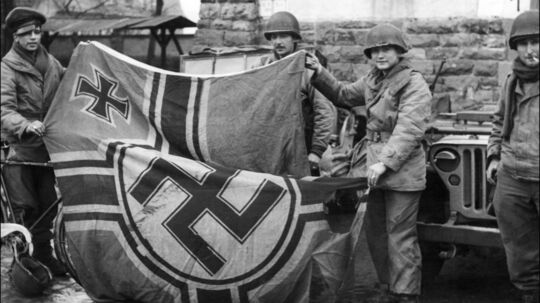 Photo datÈe de fÈvrier 1945 de soldats amricains tenant un drapeau nazi, à Colmar, aprËs avoir libÈrÈ la ville avec l'armÈe franÁaise durant la seconde guerre mondiale. // Picture dated February 1945 showing American soldiers holding a Nazi flag in Colmar, East of France, after the city was captured by American infantry and French army during the World War II. // MF13 - 19450201 - COLMAR, FRANCE : Picture dated February 1945 showing American soldiers holding a Nazi flag in Colmar, East of France, after the city was captured by American infantry and French army during the World War II. From L to R: Private Richard Ronca, wearing a German cap, of Norristown, Pennsylvania, Private William Higgins of Yonkers, New-York, and Private Robert Tyhurst of Leopard, Missouri. // AFP PHOTO AFP/STF/SE