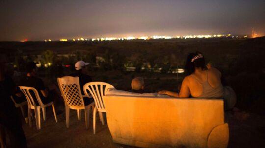 Nogen ser fodbold. Men en gruppe israelere sætter sig tilrette for at se beskydningen af Gaza.