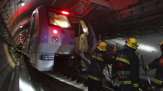 Redningsfolk igang med at evakuere passagerer fra undergrundstoger på Linje 10 i Shanghai tirsdag.