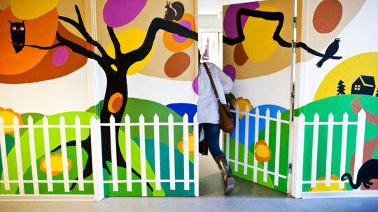 Optiske bedrag på danske demensafsnit er i hastig vækst. Indretningen i Pilehuset er en af de vigtigste ting for at beboerne føler sig godt tilpas. Blandt andet er denne dør maskeret af en vægmaleri, der umiddelbart indikerer at man kan komme igennem det hvide stakit. Og det virker. Kun medarbejderne bruger denne dør.