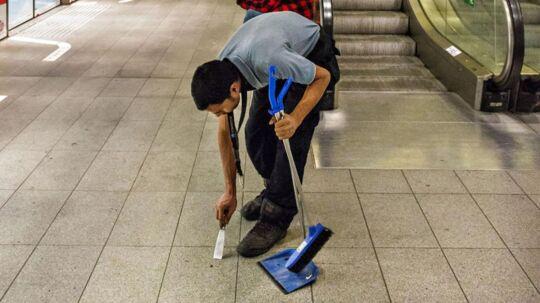 Arkivfoto: Rengøring om natten på Metro station Kongens Nytorv Rengøringsmand med kost og fejeblad