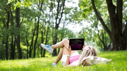 Roen sænker sig, når man lægger sig i skovbunden med sin tavle-PC og kan høre musik eller gå på nettet. Men bag kulisserne foregår der en særdeles heftig kamp mellem teleselskaberne, som konstant forsøger at finde på nyskabelser, der holder på kunderne - og helst napper nogle af konkurrenternes. Arkivfoto: Iris/Scanpix