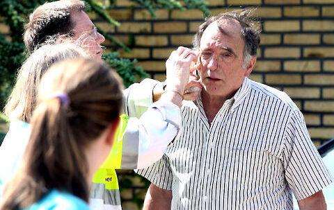 Paul Wachtel bliver behandlet foran sit hjem efter røveriet den 30. maj.