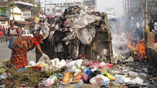 Kvinder samler affald på GS Road, en af hovedvejene i den indiske by Guwahati.