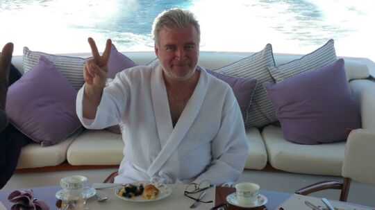 Lars Seier Christensen spiser morgenmad om bord på sin yacht d'Angleterre ud for Cannes i Sydfrankrig. Han har været oppe hele natten og fulgt den dramatiske Brexit-afstemning på tv'et ombord, men har dog ingen intentioner om at indhente den forsømte nattesøvn, for som han siger: »Nu skal vi have champagne!«