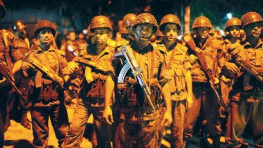 Sikkerhedsstyrker står nær caféen, hvor omkring 20 mennesker holdes som gidsel i Bangladeshs hovedstad, Dhaka.