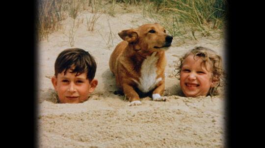 En otte-årig prins Charles og hans seks år gamle søster prinsesse Anne fotograferet på Holkham Beach i 1957 efter, at deres far - prins Philip - har begravet dem i sand til halsen. Det er deres mor, dronning Elisabeth, der tager billedet.