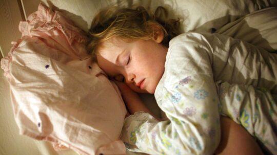 Modelfoto: Et barn sover med hovedet på puden.