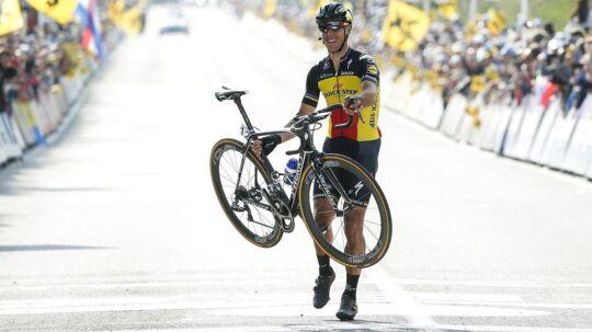 Gilbert bar sin cykel over målstregen i Flandern Rundt.