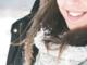 brunette girl smiling, snow on her hair