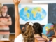 Schoolgirl rising her hand at geography lesson-front